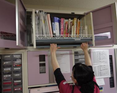 ダウンウォール機能により最上段の棚に収納したマニュアルを簡単に取り出せる様子1