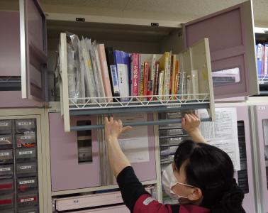 ダウンウォール機能により最上段の棚に収納したマニュアルを簡単に取り出せる様子2